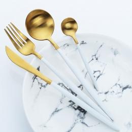 Luksusowa zastawa stołowa ze stali nierdzewnej eleganckie połyskujące sztućce z nowoczesnymi białymi rączkami złota srebrna